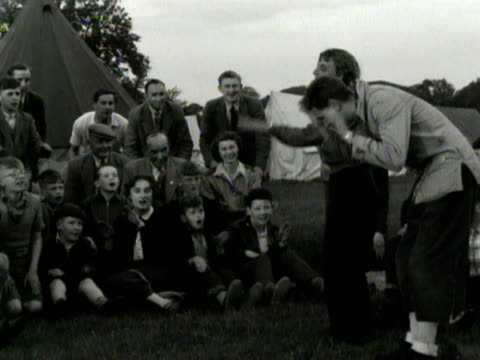 A camp site worker leads a large group of people in a singalong around a camp fire 1954