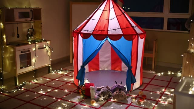 camp tent in child playroom at night illuminated - luminosità video stock e b–roll
