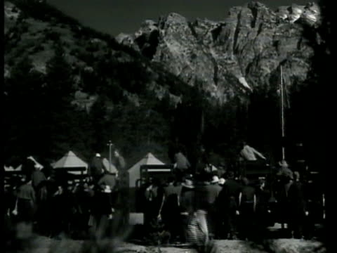 camp w/ men lined up mountain bg men climbing onto back of trucks tents mountains bg truck carrying men around a bend men piling off back of truck... - civilian conservation corps video stock e b–roll