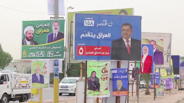 vídeos de stock e filmes b-roll de campaign posters adorn walls and posts in the streets of basra including some for a former member of the hashed alshaabi paramilitary units - bassorá