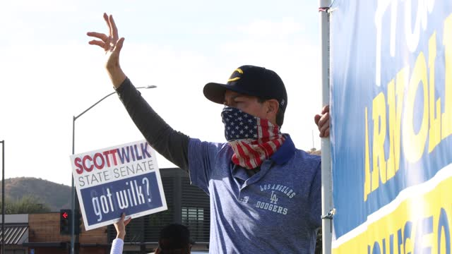 campaign supporters wearing masks hold up signs on a street corner during election day as voters head to polls on election day on november 3 in santa... - santa clarita stock videos & royalty-free footage