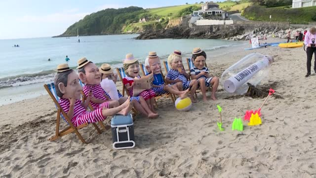 campaigners from uk-based anti-poverty organisation oxfam pose as g7 leaders wearing swimsuits and relaxing on deckchairs on a beach in falmouth, 25... - swimwear stock videos & royalty-free footage