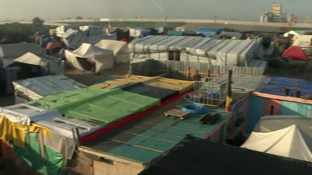 vídeos y material grabado en eventos de stock de campaigners lose high court challenge to government refugee policy; t25101611 - france: calais: jungle refugee camp buildings - channel 4 news