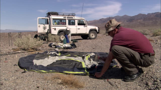 a camper begins setting up a tent in death valley. - land rover stock videos & royalty-free footage