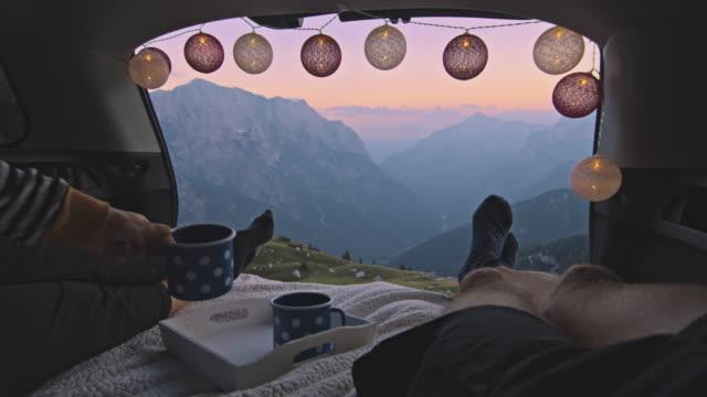 vídeos y material grabado en eventos de stock de slo mo camper pareja disfrutando del té de la noche desde el maletero del coche - taza sin platillo