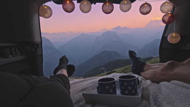 slo mo camper couple resting and enjoying the sunset in mountains from the car trunk - tree trunk stock videos & royalty-free footage