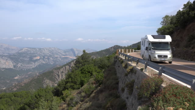 pan / a camper on mountain road at supramonte mountain - camper van stock videos & royalty-free footage