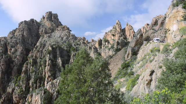ws a camper on the road through the fantastic rock landscape of the calanche of piana, unesco world heritage site / gulf of porto, corsica, france - igneous stock videos & royalty-free footage