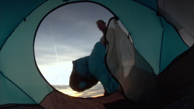 A camper pitches his sleeping bag into his tent.