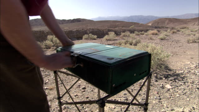 a camper sets up a gas camp stove in the desert. - キャンプ用ストーブ点の映像素材/bロール