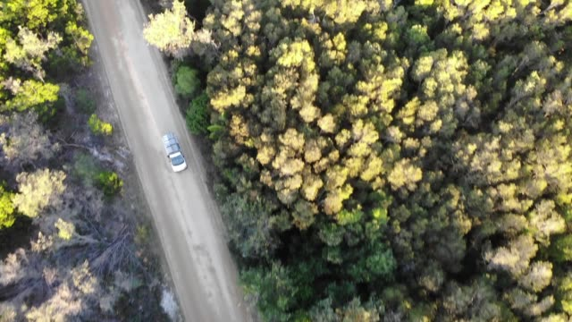 camper van driving on the road shot from above with a drone - lieferwagen stock-videos und b-roll-filmmaterial