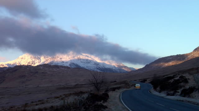 ws camper van driving through road at dawn, cloud covered mountains in background / capel curig, snowdonia, uk - snowdonia stock videos & royalty-free footage
