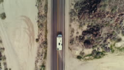 A camper van driving through the Mojave desert on a summer day
