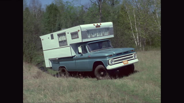 ws pan camper van moving through forest area / united states - camper van stock videos and b-roll footage