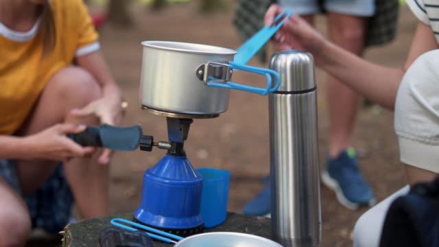 vidéos et rushes de les campeurs font bouillir l'eau sur une boîte de gaz - tente