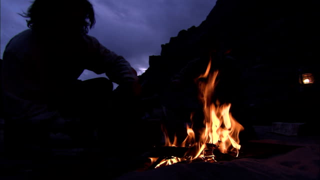 campers converse over a fire at night. - lagerfeuer stock-videos und b-roll-filmmaterial