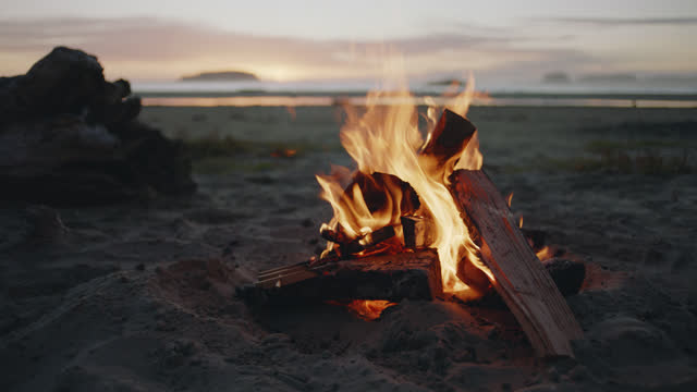 slo mo. a campfire burns on a scenic tofino beach at sunset. - camp fire stock videos & royalty-free footage