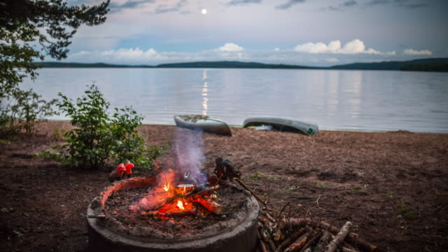 Campfire next to a lake in the wilderness