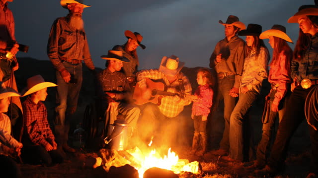 campfire singalong with cowboys and cowgirls at night - guitar stock videos & royalty-free footage