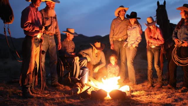 vídeos de stock, filmes e b-roll de fogueira com cowboys e cowgirls à noite - rancho