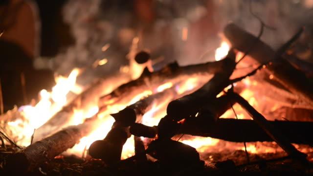 Lagerfeuer mit nicht erkennbare Personen im Hintergrund