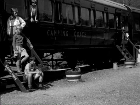 ms camping coach train standing at station, boys having picnic on platform; playing games on grass beside train and in river and waving at passing train with level crossing / gara bridge, devon, england - boy scout stock videos and b-roll footage