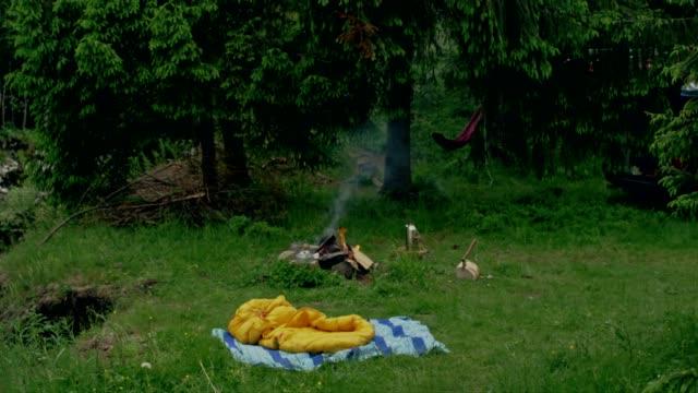 山でキャンプ。ハンモック、焚き火 - 寝袋点の映像素材/bロール