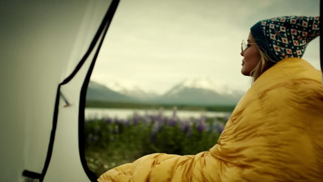 Camping in the wild. Woman admiring view from a tent
