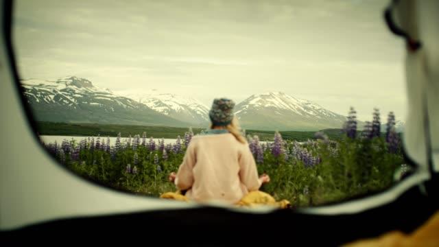 野生のキャンプ。女性はテントの中からの景色を眺め - 寝袋点の映像素材/bロール