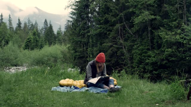 Camping in the wild. Woman reading on a meadow