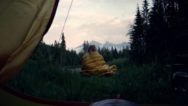 野生のキャンプ。テントの前に座っている女性 - 寝袋点の映像素材/bロール