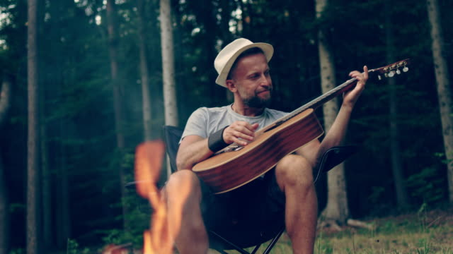 camping. man relaxing with guitar - camp fire stock videos and b-roll footage