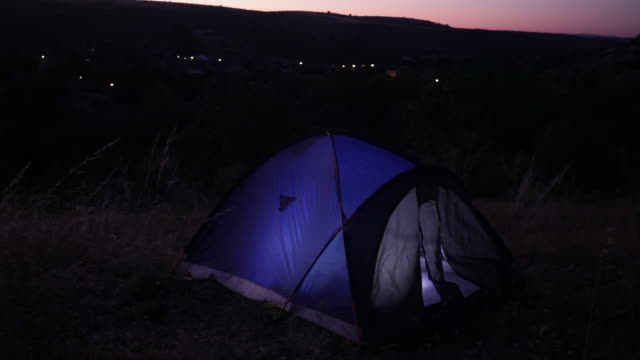 camping. night shot with tent illuminated from the inside.  spain, countryside of segovia. - segovia stock videos & royalty-free footage