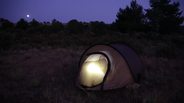 camping. night shot with tent illuminated from the inside.  spain, countryside of segovia. - electric torch stock videos & royalty-free footage