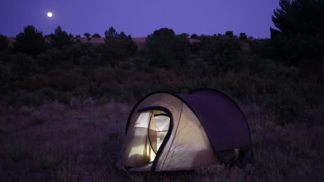 camping. night shot with tent illuminated from the inside.  spain, countryside of segovia. - tent stock videos and b-roll footage