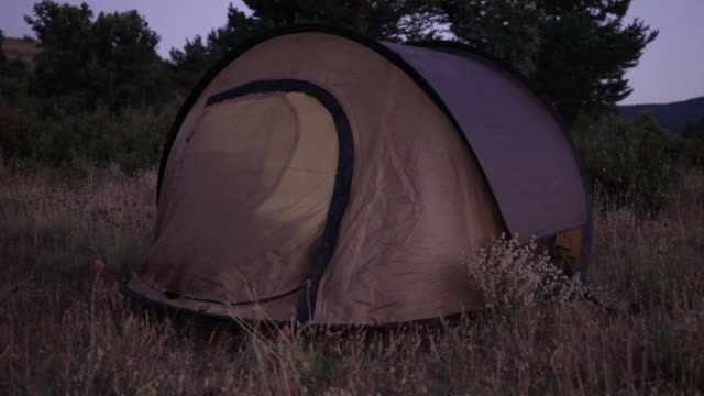 camping. night shot with tent illuminated from the inside.  spain, countryside of segovia. - convenience stock videos & royalty-free footage