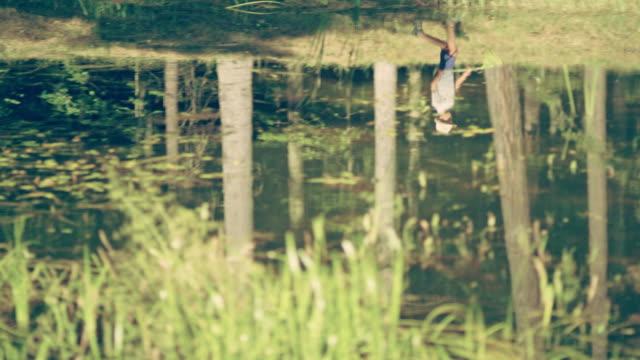 vídeos de stock, filmes e b-roll de o camping refletindo na superfície da água. garoto andando ao longo da costa - lago reflection