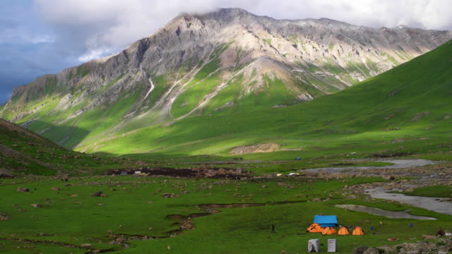 a camping site amidst the massive himalayas during the summer lush green season as seen from the vishansar or vishnusar lake, an alpine high altitude oligotrophic lake - etnia indo asiatica video stock e b–roll