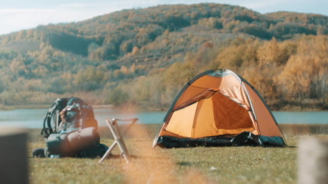 camping site by lake - zaino da montagna video stock e b–roll