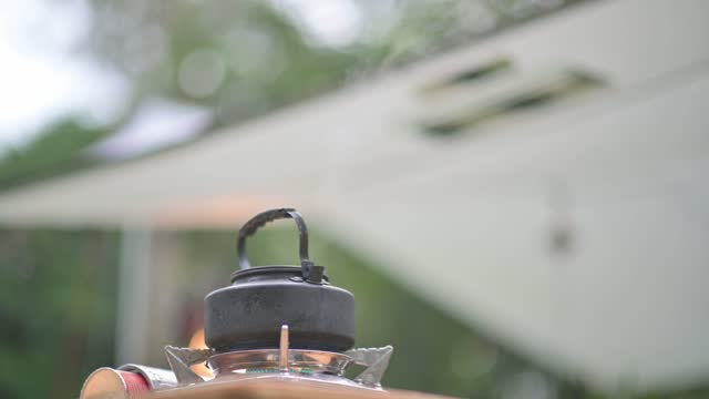 camping stove hot kettle boiling on picnic table in the morning - hob stock videos & royalty-free footage