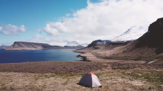 stockvideo's en b-roll-footage met camping tent staand op het rotsmassief in ijsland, drone oogpunt - ver