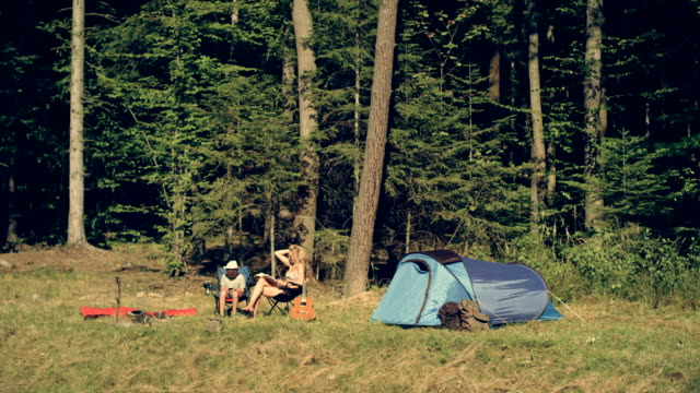 Camping. Woman and her son relaxing on the meadow