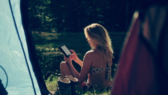 Camping. Woman relaxing with e-reader
