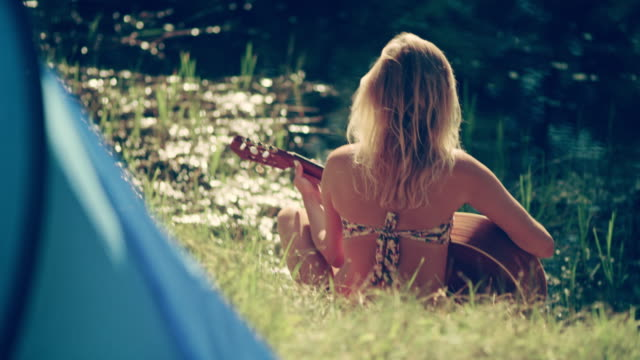 Camping. Woman relaxing with guitar