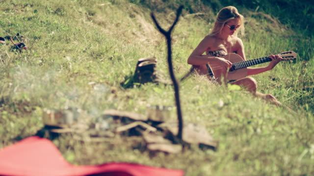 vídeos de stock, filmes e b-roll de acampar. mulher, relaxante com guitarra - área arborizada