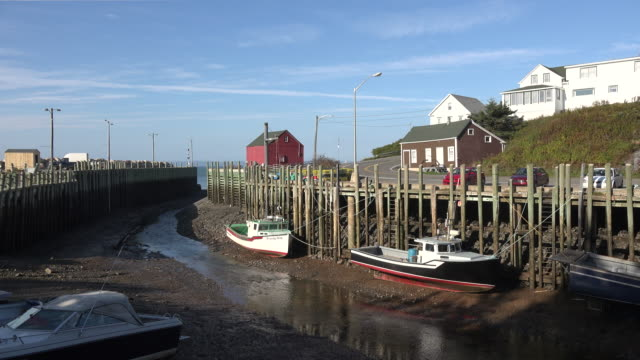Canada Bay of Fundy boats docked Halls Harbour fluffy clouds low tide