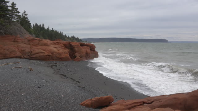 Canada Bay of Fundy red rocks and pebble beach
