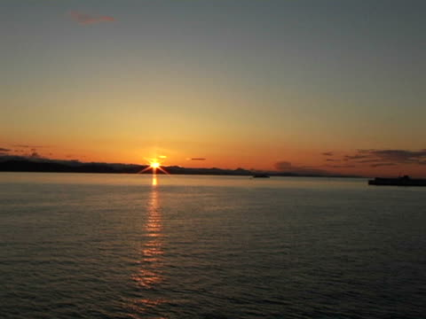 WS, Canada, British Columbia, Silhouette of ship traveling in ocean at sunset