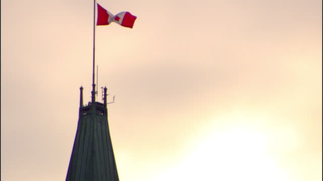 Canada flag attached to pole atop roof of Peace Tower on Parliament Hill flag moving gently in wind National symbol pride Centre Block