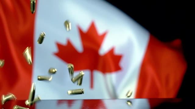 vidéos et rushes de drapeau du canada derrière des balles tombant au ralenti - crime organisé